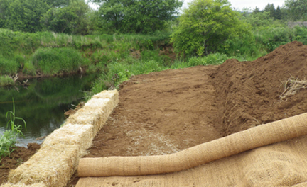 Straw bales and burlap help prevent loose soil from washing into the river.